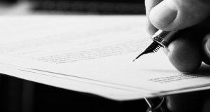 ink pen in hand above paper